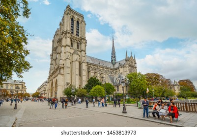 Paris, France - September 23 2018: The gothic Notre Dame Cathedral on ile de la cite in Paris France with tourists and clouds in autumn, taken from the Pont au Double bridge