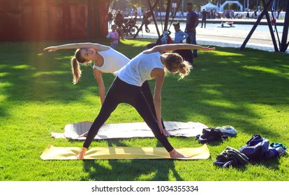 PARIS, FRANCE - SEPTEMBER 23dr, 2017 : Two girls practicing yoga in the park in Paris, France
