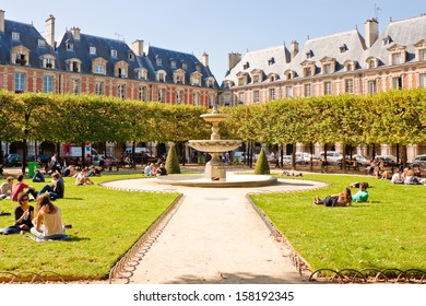PARIS, FRANCE - SEPTEMBER, 24: People relaxing on green lawns of the famous Place des Vosges - the oldest planned square in Paris located in Marais district on September 24, 2013 in Paris.