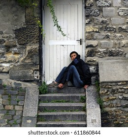 Paris, France - September 25, 2008: a homeless of asian origin is sitting by the closed door of a house at Montmartre