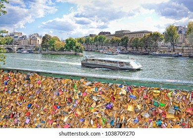 PARIS, FRANCE - SEPTEMBER 25, 2015:  - a lot of padlocks on the bridge, a boat croses the River of Seine in autumn in Paris France