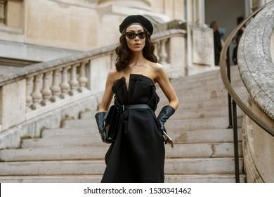 PARIS, FRANCE - SEPTEMBER 25, 2019: A guest wearing a beret and black Maison Margiela dress seen outside MAISON MARGIELA show, during Paris Fashion Week Womenswear Spring/Summer 2020.