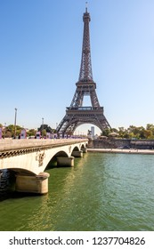 PARIS, FRANCE - SEPTEMBER 27, 2018: View to Eiffel Tower during midday near the river Seine. People on the bridge are looking at the tall building. Touristic idea