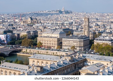 PARIS, FRANCE - SEPTEMBER 28, 2018: Paris cityscape with a wide angle perspective. Cloudy day with bright sunlight. Dark blue tone on the buildings and cool whitebalance