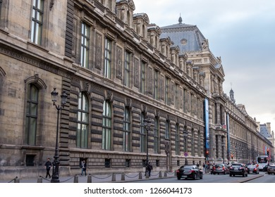 PARIS, FRANCE - SEPTEMBER 28, 2018: People walking on the streets during a cloudy day. Big museum in the background. French roads