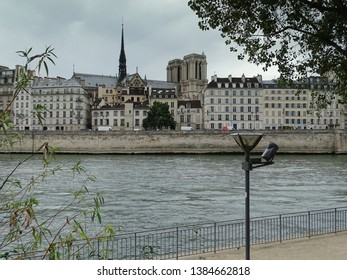 Paris / France - September 30 2016: Bit posterized skyline with Siene river embankment in Paris, historical buildings and Notre Dame cathedral towers behind them, tree  benches in foreground