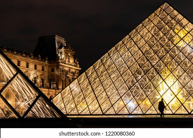 Paris, France - September 30, 2018: Bright light glass pyramids with silhouette walking people of Lourve museum at night.