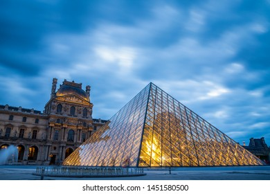 Paris, France - September 30, 2018: Iconic glass pyramid of Louvre museum with blurry motion of blue cloudy sky at sunset.