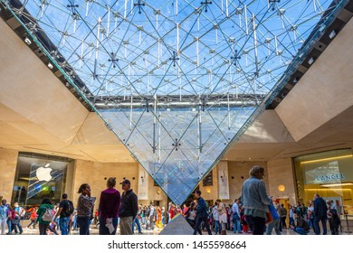 Paris, France - September 30, 2018: Crowd walking around the inverted glass pyramid inside underground department store under the iconic pyramid of Louvre museum.