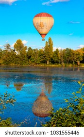 PARIS, FRANCE - SEPTEMBER 30th, 2017 : hot-air balloon flying over a lake in the french countryside near capital.