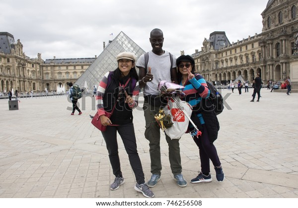 PARIS, FRANCE - SEPTEMBER 5: Asain women mother and daughter buying souvenir gift from African-French Louvre Pyramid at Musee du Louvre or the Grand Louvre Museum on September 5, 2017 in Paris, France