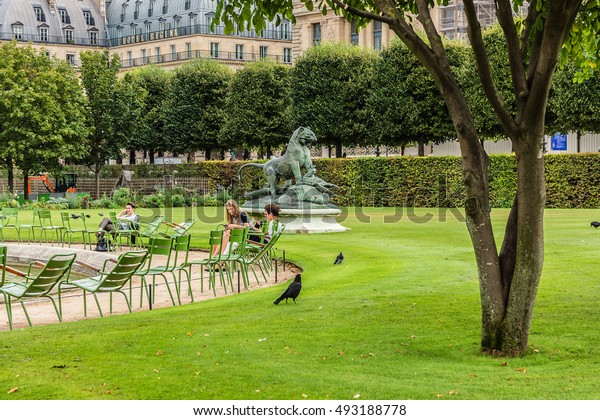 PARIS, FRANCE - SEPTEMBER 6, 2016: Jardin des Tuileries (Tuileries garden) - favorite spot for rest of tourists and Parisians on the Sunset. Garden was created by Catherine de Medici in 1564.