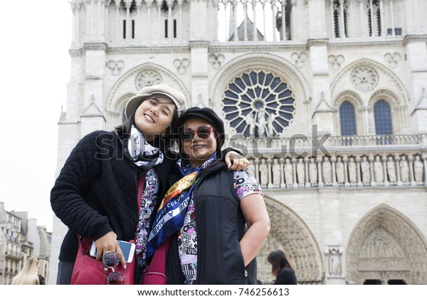 PARIS, FRANCE - SEPTEMBER 6 : Asain women mother and daughter travel and posing for take photo with Cathedrale Notre-Dame de Parison September 6, 2017 in Paris, France