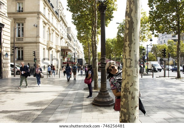 PARIS, FRANCE - SEPTEMBER 6 : Asian thai women playful and travel visit at sidewalk in L avenue des Champs-Elysees on September 6, 2017 in Paris, France