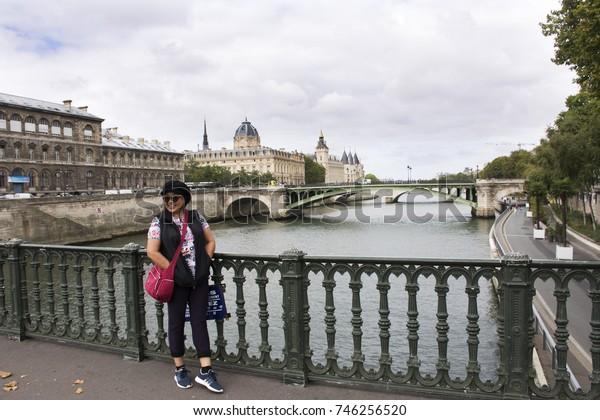 PARIS, FRANCE - SEPTEMBER 6 : Old woman posing for take photo on bridge crossover Seine river on September 6, 2017 in Paris, France