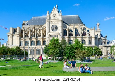 PARIS, FRANCE - SEPTEMBER 7, 2018: Unknown people rest on green lawn near Catholic Church of St. Eustache, or Saint-Eustache (Église Saint-Eustache), Paris, France