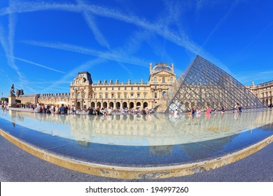 PARIS, FRANCE - SEPTEMBER 8, 2012: The entrance to Louvre -  glass pyramid fountain. Tourists resting on granite fence fountain. Traces in the sky jet