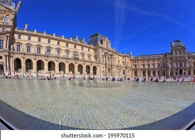 PARIS, FRANCE - SEPTEMBER 8, 2012: The entrance to Louvre -  glass pyramid fountain. Tourists resting on granite fence fountain. Traces in the sky jet. Picture taken Fisheye lens