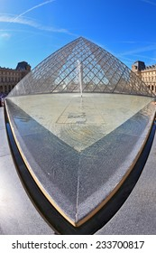 PARIS, FRANCE - SEPTEMBER 8, 2012: The world-famous entrance to  Louvre - the glass pyramid and spectacular fountain. Picture taken Fisheye lens