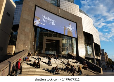 PARIS, FRANCE - SEPTEMBER 8, 2019: New season in Opera Bastille (Madame Butterfly by Puccini advertised on screen on facade). Arts and urban scene. People sitting on steps - popular meeting point.