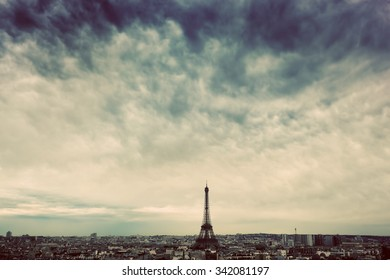 Paris, France skyline with Eiffel Tower under dark dramatic clouds. Artistic vintage, retro mood