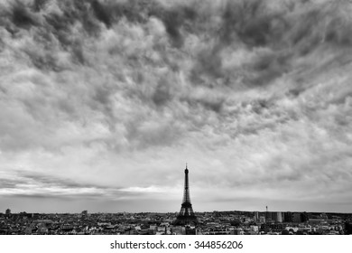 Paris, France skyline with Eiffel Tower under dark dramatic clouds. Black and white.