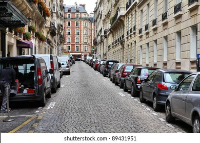 Paris, France - typical old city street. Cars parked along cobblestone way.