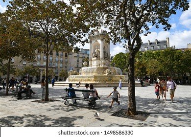 Paris, France-08 10 2019:People sitting on benches and strolling around the Saint Sulpice fountain in the Odéon Quarter of the 6th arrondissement of Paris, France.