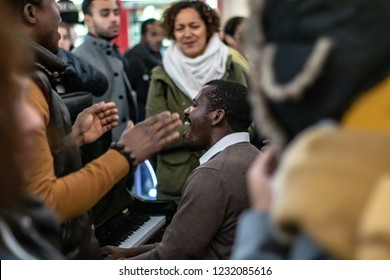 Paris, France-11.16.2018: Men singing gospel music at piano attract a crowd in Saint Lazare Station. Man singing at the piano gospel music.