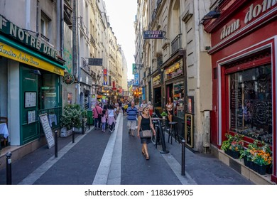 Paris, France-August 17, 2018: a typical street in the Latin Quarter of Paris on the left bank of the river Seine with book shops, cafes and restaurants and tourists on a summers day in 2018