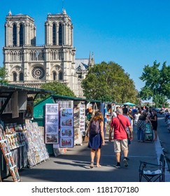 Paris, France-August 18, 2018: typical scene  on the left bank of the river same with traditional booksellers and tourists, with Notre Dame Cathedral in the background on a blue sky day