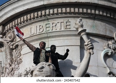 PARIS, FRANCE-JANUARY 11, 2015: Black and arab people waving the French flag  during manifestation on Republic Square in Paris against terrorism after the attack against newspaper Charlie Hebdo.
