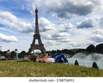 Paris, France/June 2020: While Europe is struggling with coronavirus pandemic,  parisians are laying on the grass at champ de mars and around Eiffel Tower in a sweltry day without abiding by measures.