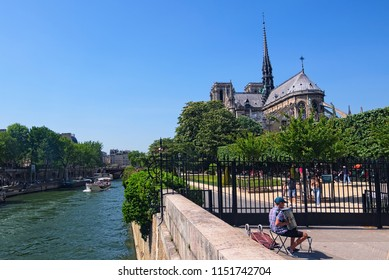 Paris, France-MAY 06, 2018: Romantic paris. Accordion player near Notre-Dame Cathedral at sunny day.