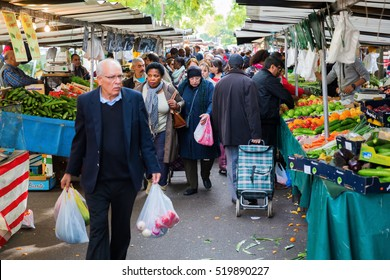 Paris, France-October 18, 2016: street market in Belleville with unidentified people. Its a large and popular outdoor market along Boulevard de Belleville with many local farmers selling their produce
