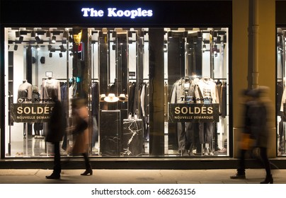 PARIS - JANUARY 14, 2017: View of people walking in blurry motion in front of fashion brand store at night in Le Marais district of Paris. Sale season and consumerism concept.