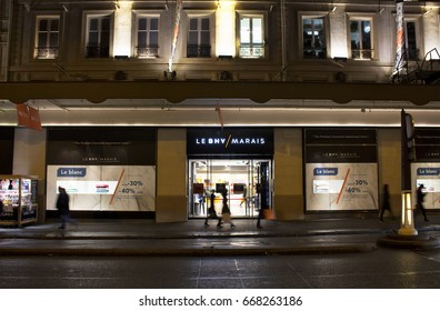 PARIS - JANUARY 14, 2017: View of people walking in blurry motion in front of a famous department store at night in Le Marais district of Paris. Sale season and consumerism concept.