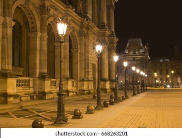"PARIS - JANUARY 17, 2017: Night view of street lights and Louvre Museum (Musee du Louvre). Former historic palace housing huge art collection, from Roman sculptures to da Vinci's ""Mona Lisa."""