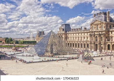 PARIS - JULY 21: The Louvre museum and the pyramid on July 21, 2013 in Paris, France. The Louvre was once a palace and is now a museum. The pyramid serves as an entrance to the museum.