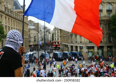 PARIS - JULY 26, 2014: A masked protester holding a French flag overlooks a line of riot police facing a crowd of people at a pro-Palestine protest at Place de la Republique in Paris on July 26, 2014.