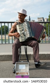 PARIS - JULY 6: Unidentified senior musician play accordion on the bridge on July 6, 2013 in Paris, France. Dozens buskers perform on the streets and in the metro of Paris.