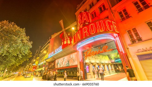 PARIS - JUNE 11: The Moulin Rouge by night, on June 11, 2014 in Paris, France. Moulin Rouge is a famous cabaret built in 1889, locating in the Paris red-light district of Pigalle.
