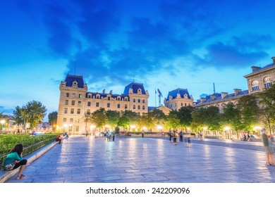 PARIS - JUNE 21, 2014: Tourists enjoy summer night lights in the square of Notre Dame. More than 30 million people visit the city every year.