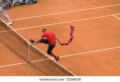 PARIS - JUNE 7: An unidentified spectator runs onto the tennis court with a flag in his hand at Roland Garros French Open tennis tournament on June 7, 2009 in Paris.