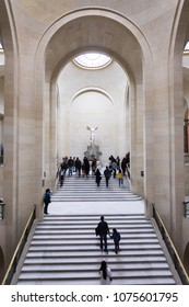 Paris, Louvre Museum. The Victory of Samothrace - Nike of Samothrace: marble sculpture of the Greek goddess of Victory, resembling a winged woman. Tourists walking through the museum. Paris Feb 2018