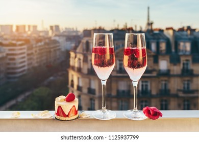 Paris luxury lifestyle. Pink champagne with rasberries in two glasses, traditional french cake with strawberries on a balcony with a view on rooftops and Eiffel Tower on the sunset