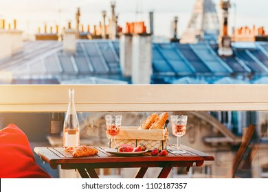Paris luxury lifestyle. Pink wine in two glasses, traditional french bakery products - baguettes, macaron, croissant and strawberries on a balcony with a view on rooftops and Eiffel Tower