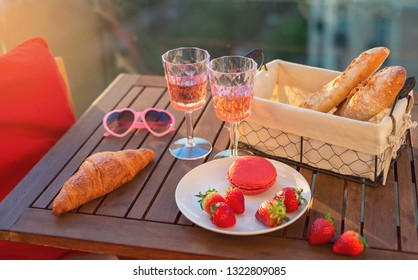Paris luxury lifestyle. Pink wine in two glasses, traditional french bakery products - baguettes, macaron, croissant and strawberries on a balcony at sunset