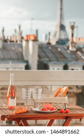 Paris luxury lifestyle. Pink wine, two glasses, traditional french bakery products - baguettes, macaron, croissant and strawberries on a balcony with a view on rooftops and Eiffel Tower.