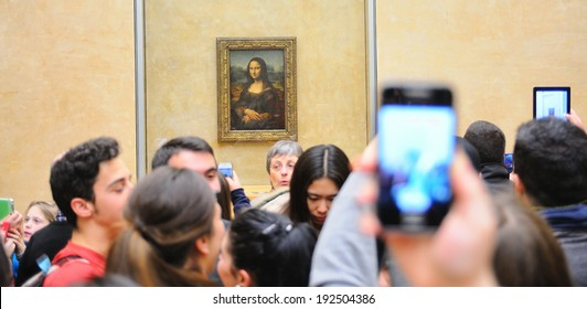 PARIS - MAR 3: Tourists take pictures the Mona Lisa (Monna Lisa or La Gioconda in Italian and La Joconde in French) painting at the Louvre Museum on March 3, 2014 in Paris, France.